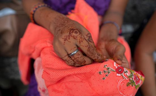 A woman's hands embroidering some cloth